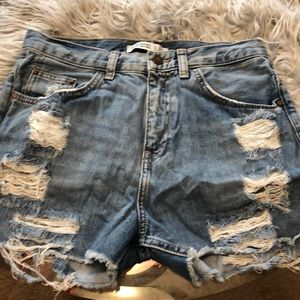 Ripped light blue jean shorts with stud details